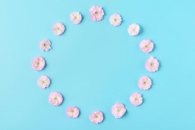 Frame gemaakt van roze kersen bloeiende veldboeket patroon op blauwe achtergrond. plat leggen. bovenaanzicht. valentijnsdag achtergrond