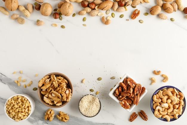 Frame gemaakt van verschillende soorten noten in kommen. bovenaanzicht kopieer ruimte