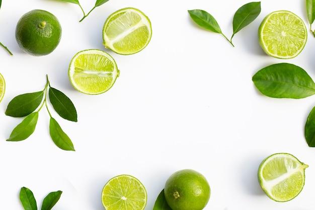 Frame gemaakt van verse limoenen (lemmetjes) met groene bladeren op een witte achtergrond. bovenaanzicht