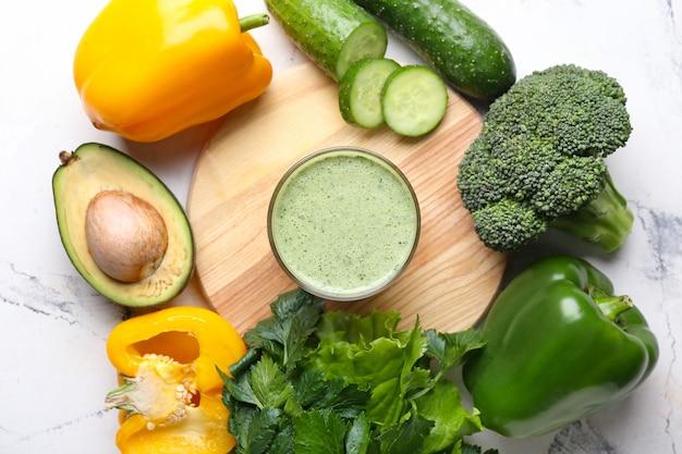 Frame gemaakt van verse smoothie en groenten op lichte ondergrond