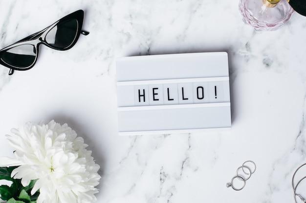 Frame hallo op een marmeren tafel met een bloem en glazen
