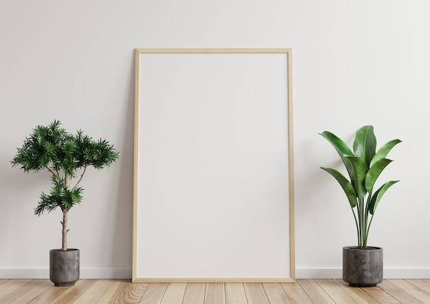 Frame in de kamer, witte muur op de houten vloer, mooi patroon, versierd met planten aan de zijkant.
