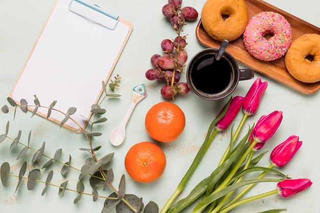 Frame-klembord met zoete koffiepauze en bloemen