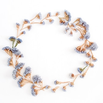 Frame krans van lichtblauwe gedroogde bloemen op witte achtergrond. platliggend, bovenaanzicht