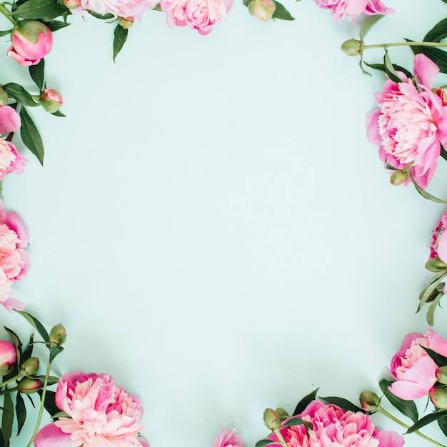 Frame krans van roze pioenroos bloemen, takken, bladeren en bloemblaadjes