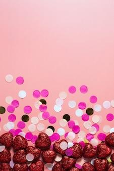 Frame. lege kaart voor valentijnsdag. op een roze achtergrond confetti en rode harten. grappige gefeliciteerd. plat lag, bovenaanzicht. rode glanzende harten.