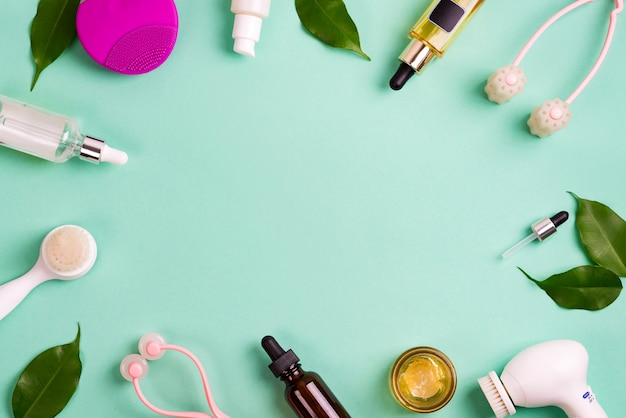 Frame met accessoires voor gezichtsverzorging en groene bladeren. reinig de huid met een andere borstel, fles met olie, zuur en crème en op een groene