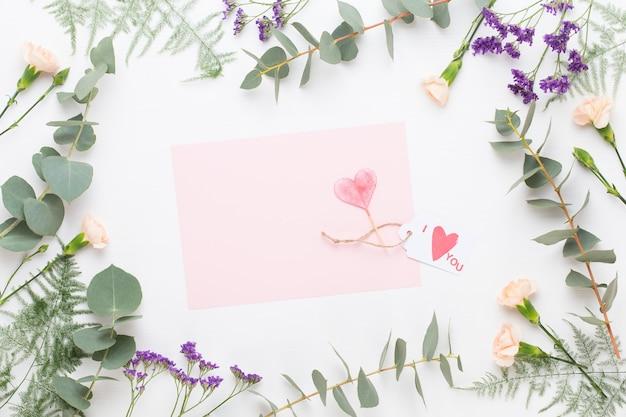 Frame met bladeren en bloemen en brief met hart in het midden