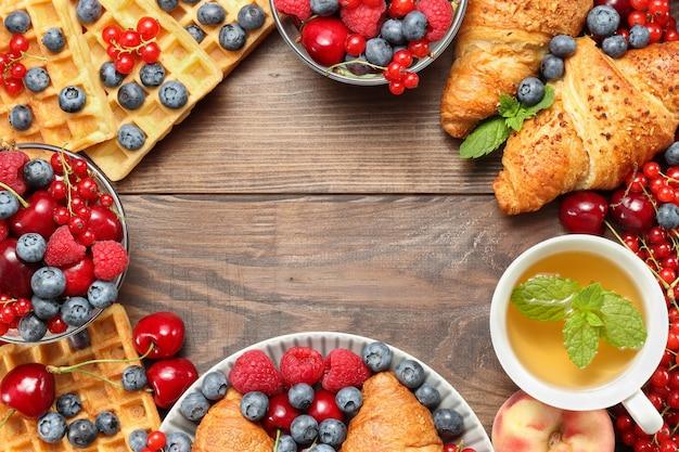 Frame met croissants, wafels, bessen en fruit met kopje thee op de bruine houten achtergrond