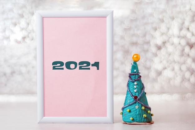 Frame met de inscriptie 2021 met een handgemaakte kerstboom