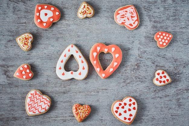 Frame met geglazuurde en versieren hart vorm cookies op grijze achtergrond. valentijnsdag eten concept