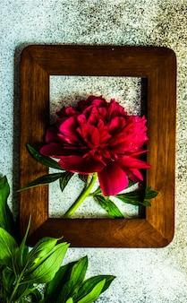 Frame met heldere rode pioenroos bloemen op betonnen tafel