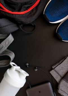 Frame met het beeld van een sportuniform, schoenen, rugzak, tops, tieten, shaker, koptelefoon