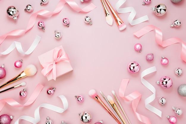 Frame met kerstbal, cadeau, lint, cosmetica en decoraties in pastelroze kleur. vakantie achtergrond. schoonheidsconcept. platliggend, bovenaanzicht