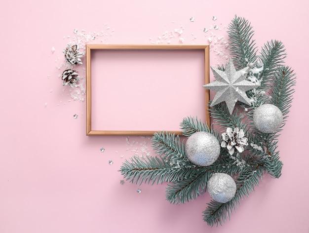 Frame met kerstboomtakken en kerstversiering op zacht roze