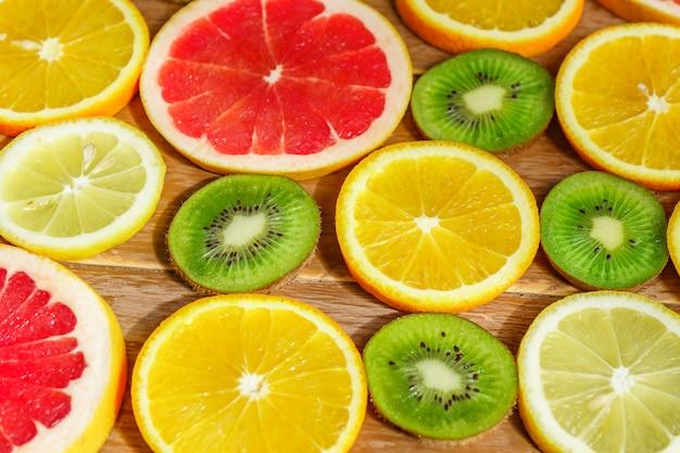 Frame met plak van sinaasappelen, citroenen, kiwi, geïsoleerd grapefruitpatroon.