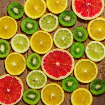Frame met plakjes sinaasappelen, citroenen, kiwi, grapefruitpatroon. kopieer ruimte