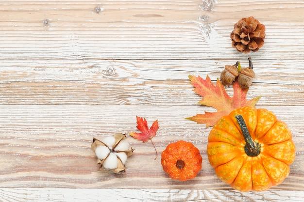 Frame met pompoenen en herfstdecoraties in de hoek op de witte houten achtergrond