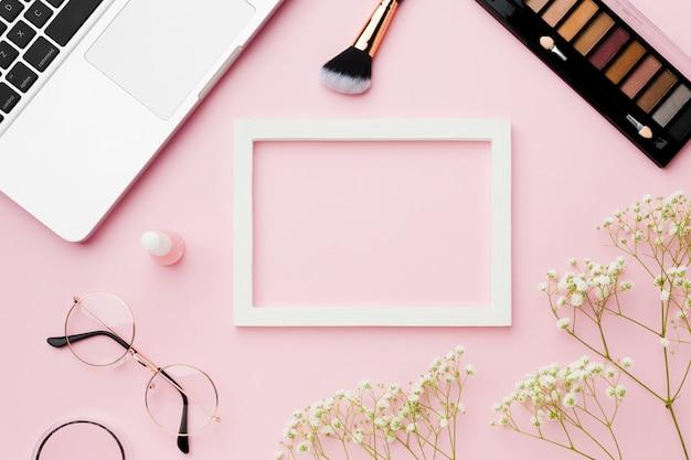 Frame omgeven door make-up en laptop