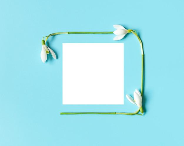 Frame op ansichtkaart van sneeuwklokjes met wit papier voor womens day of mothers day op blauwe achtergrond