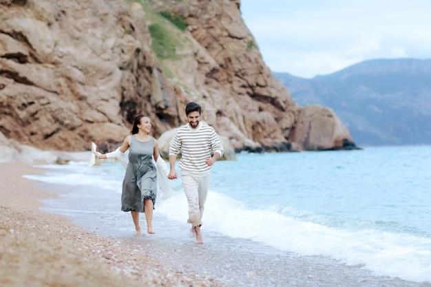 Frame shoot van een paar dat samen op het strand loopt en elkaar met de hand vasthoudt