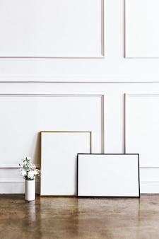 Frame tegen een witte muur bij een vaas met bloemen