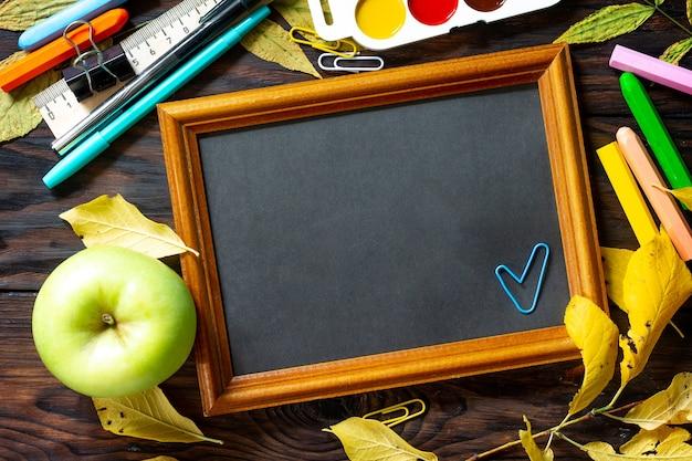 Frame terug naar school tafel met herfstbladeren appel en schoolspullen bovenaanzicht