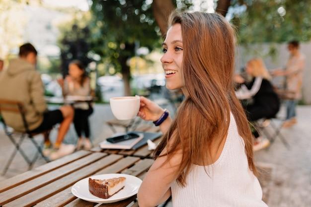 Frame van achterkant van jonge aantrekkelijke vrouw met lang haar koffie drinken op zomerterras in goede zonnige dag