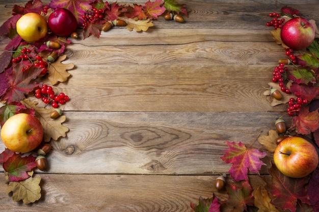 Frame van appels, eikels, bessen en herfstbladeren op donker hout