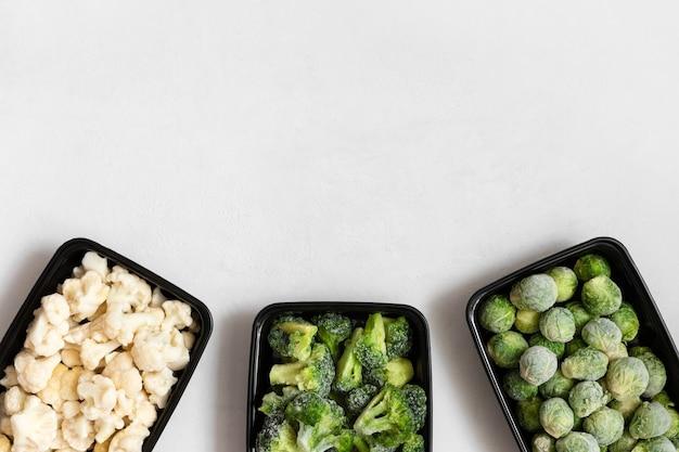 Frame van bevroren groenten in plastic bakjes op een witte achtergrond. een set van verschillende kolen. ruimte voor tekst. bovenaanzicht, plat gelegd.