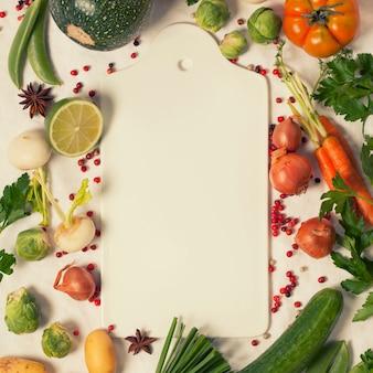 Frame van biologische groenten op witte snijplank