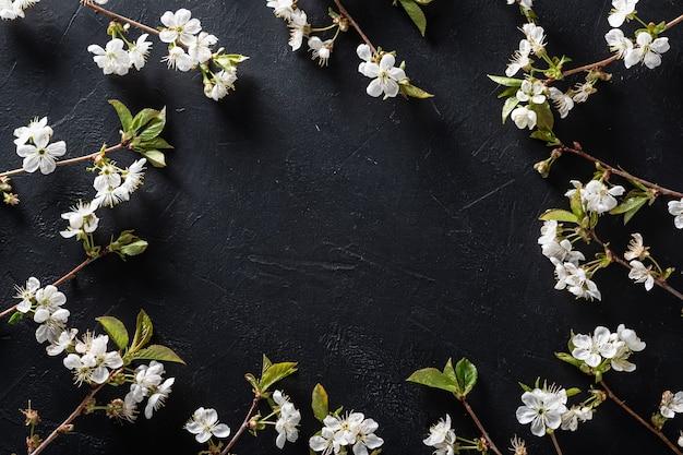 Frame van bloeiende kersen takken op een zwarte textuur tafel. plaats voor tekst