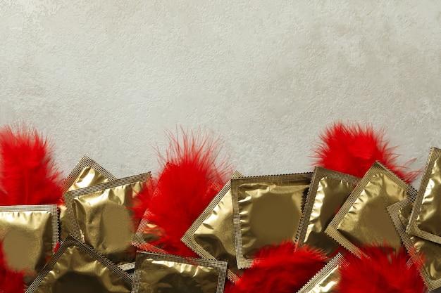 Frame van condooms met veren op witte gestructureerde achtergrond, ruimte voor tekst