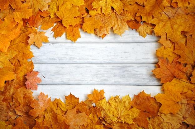Frame van de herfst, gele bladeren op een wit, houten oppervlak. herfst achtergrond.