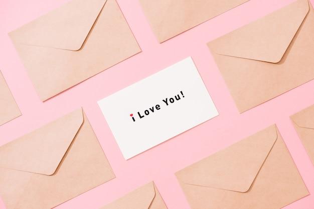Frame van enveloppen en ansichtkaart op roze tafelblad. woorden ik hou van je. valentijn concept. plat leggen.