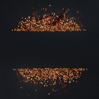 Frame van gemalen rode cayennepeper, gedroogde chili vlokken en zaden op een zwarte