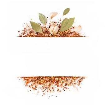 Frame van gemalen rode cayennepeper, gedroogde chili vlokken, zaden, bladeren en knoflook geïsoleerd op een witte