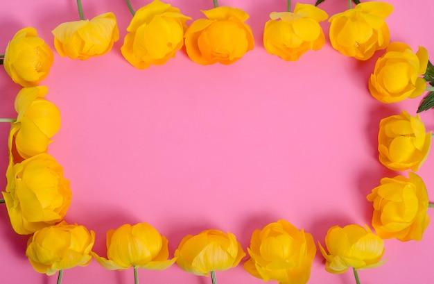 Frame van heldere gele bloemen op een roze