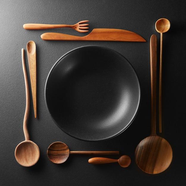Frame van het plaatsen van lege zwarte plaat en houten lepel, vork, mes op een zwarte tafel.