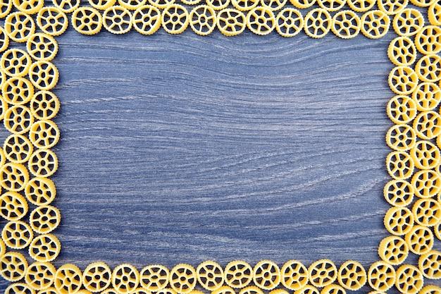 Frame van italiaanse pasta op een houten achtergrond. meelproducten bij het koken