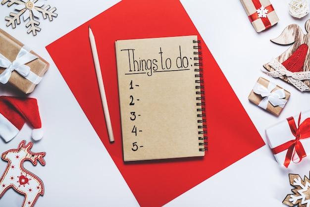 Frame van kerstboomspeelgoed en geschenkdozen en spiraalvormig notitieboekje met takenlijst in het midden