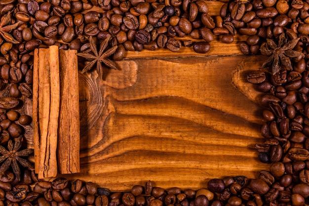 Frame van koffiebonen, steranijs en kaneelstokjes op rustieke houten tafel