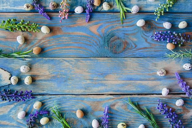 Frame van kwarteleitjes en salie bloemen op een versleten blauwe houten tafel.