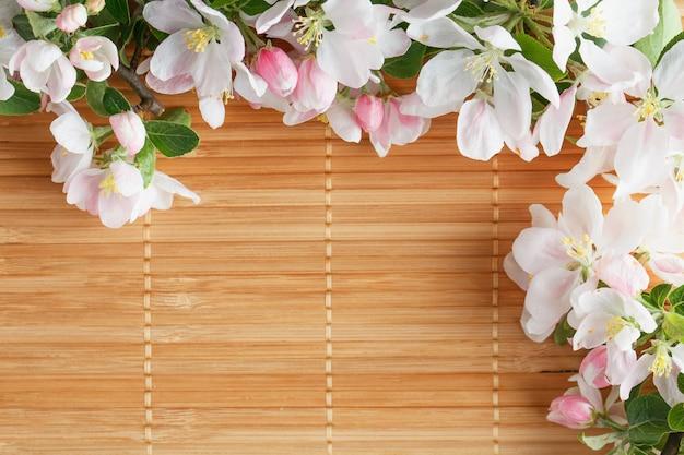 Frame van lentebloemen van sakura op bamboe