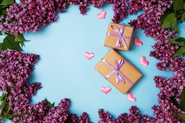 Frame van lila bloemen met twee geschenkdozen op een blauwe achtergrond
