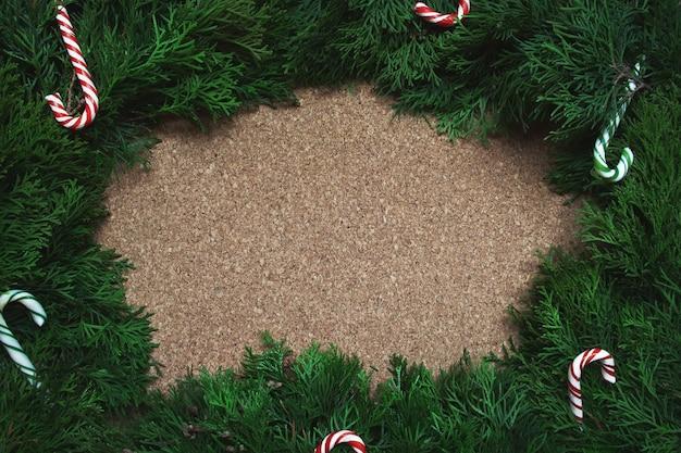 Frame van naaldboomtakken en zuurstokken op een kurkbord. kerstmis