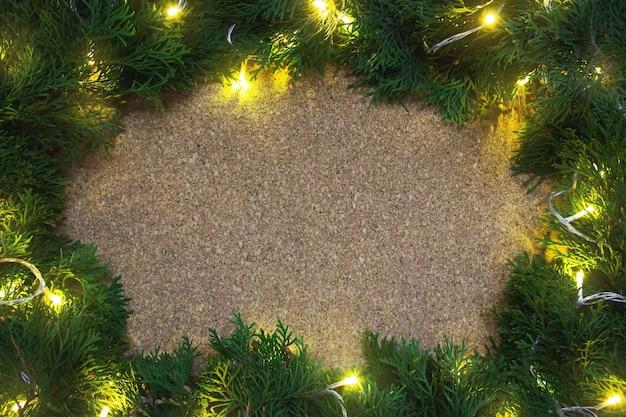 Frame van naaldboomtakken met gele lampjes op een houten bord. kerstmis