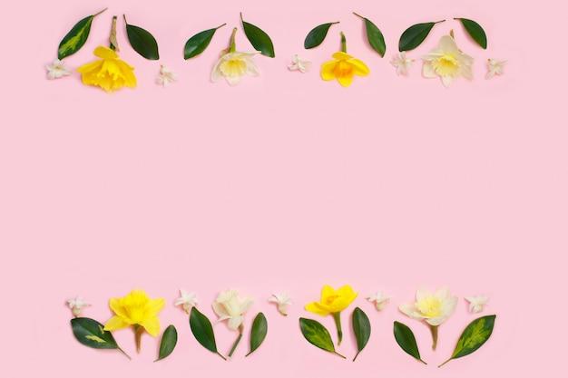 Frame van narcissen of gele narcisbloemen en bladeren op roze achtergrond