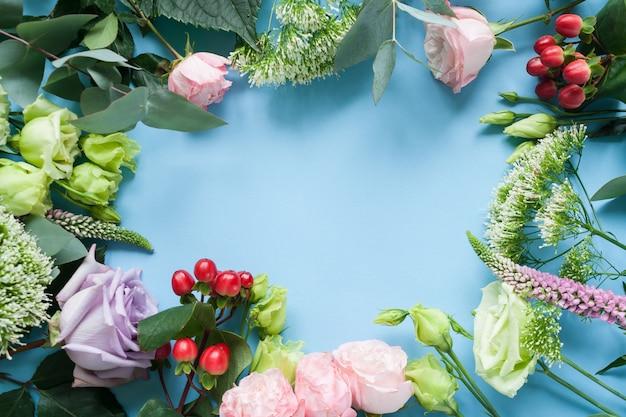 Frame van paarse en roze rozen, witte lisianthus en verschillende bloemen op blauwe achtergrond.