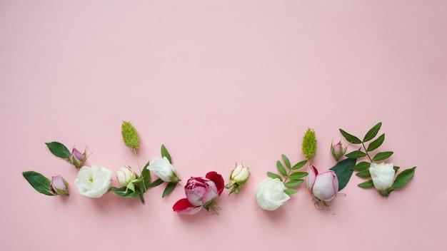 Frame van paarse en roze rozen, witte lisianthus en verschillende bloemen op roze achtergrond.